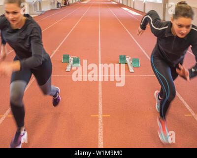 Two women running on tartan track, Offenburg, Baden-Württemberg, Germany - Stock Photo