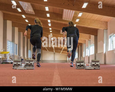 Two women running in athletics hall on tartan track, Offenburg, Baden-Württemberg, Germany - Stock Photo