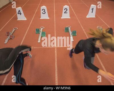 Two women runners on tartan track in starting position, Offenburg, Baden-Württemberg, Germany - Stock Photo