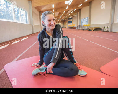 Young woman doing floor exercise in athletics hall on tartan track, Offenburg, Baden-Württemberg, Germany - Stock Photo
