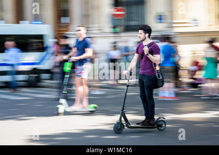 A young man rides with one hand an electric scooter at high speed, overtaking another man on an electric scooter in the streets of Paris, France. - Stock Photo