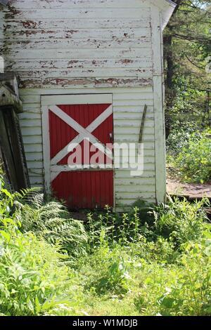 OLD  RED BARN DOOR PEELING PAINT - Stock Photo