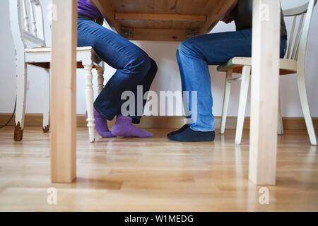 Couple sitting vis-a-vis at a table, Munich, Germany - Stock Photo