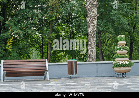 A wooden bench for rest, garbage bin for waste and basket of flowers in a city park against the background of a birch tree - Stock Photo