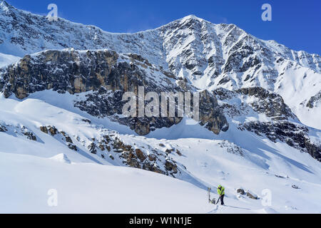 Woman back-country skiing pulling up skins, Colle di Vers, Valle Varaita, Cottian Alps, Piedmont, Italy - Stock Photo