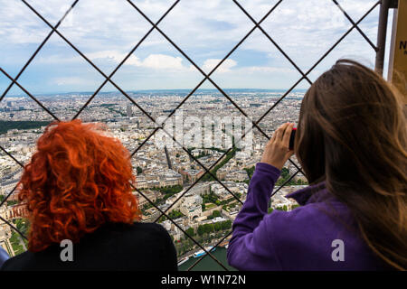 women enjoying the view from Eiffel Tower over the city of Paris, France, Europe - Stock Photo