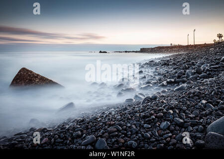 lava stone along the Atlantic coast at Puerto de la Cruz, Tenerife, Canary Islands, Spain, long time exposure - Stock Photo