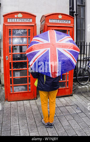 Women with Umbrella , Red Telephone Box, London, United Kingdom - Stock Photo