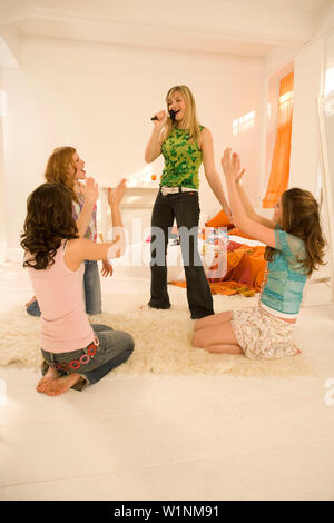 Girl (14-16) singing into make-up brush, three girls clapping hands - Stock Photo