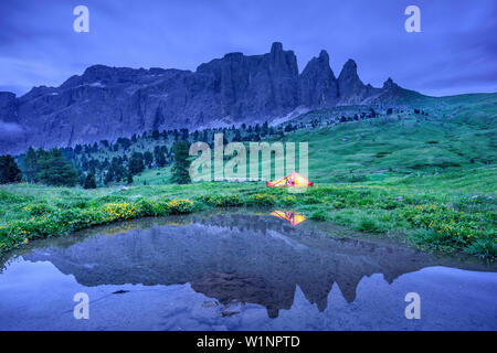Woman sitting in illuminated tent, Sella range reflecting in mountain lake, Sella range, UNESCO world heritage Dolomites, Dolomites, Trentino, Italy - Stock Photo