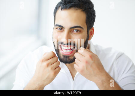 Dental Health. Man With Beautiful Smile Flossing Healthy Teeth. High Resolution Image - Stock Photo