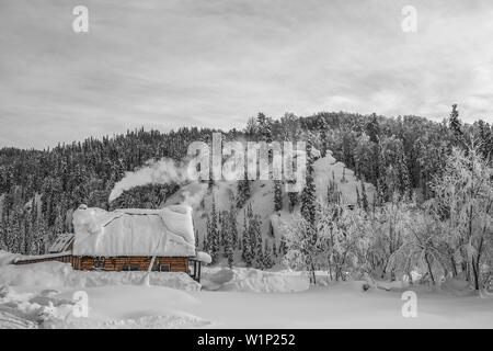 Snow-covered wooden house on the background of mountains and forests - Stock Photo