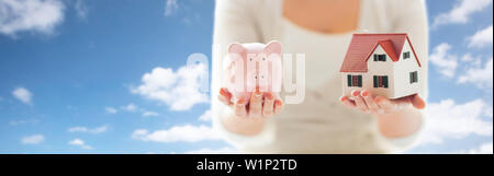 close up of woman with house model and piggy bank - Stock Photo