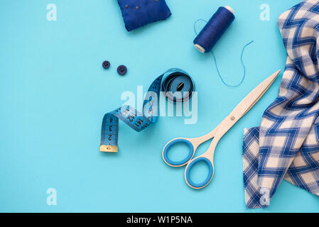 Sewing accessories with threads, scissors, pins, fabric, buttons and sewing tape on blue background. Top view. Flat lay.