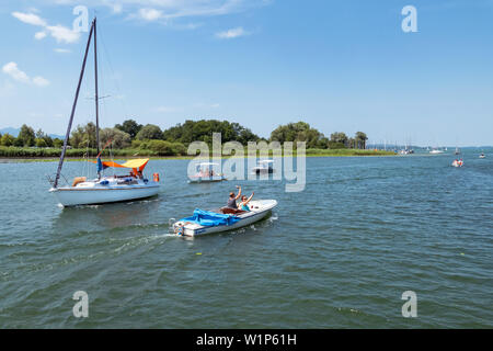 Sailing and electric boats on the Chiemsee in field - Stock Photo