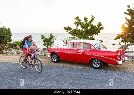 red oldtimer, woman with kid cycling along the lonely coast road from La Boca to Playa Ancon, with beautiful small beaches in between, turquoise blue - Stock Photo