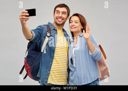 couple of tourists taking selfie by smartphone - Stock Photo