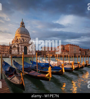 View over the Grand Canal to the Church of Santa Maria della Salute with gondolas in the morning sun and dramatic clouds, San Marco, Venice, Veneto, I - Stock Photo