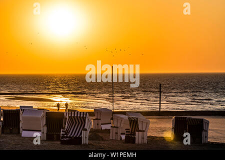 Stroller on the beach at sunset, Wangerooge, East Frisia, Lower Saxony, Germany - Stock Photo