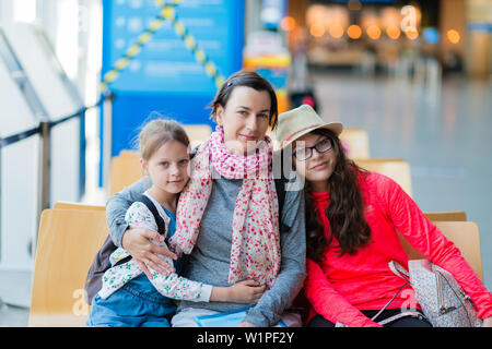 A family of three sitting in a recreation area at the airport  - mother and two daughters In airport departure lounge waiting for a flight - Stock Photo