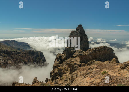 Center of Gran Canaria. Spectacular aerial view of volcanic rocks above the white fluffy clouds. Beautiful sunny day with clear, bright blue sky. Cana - Stock Photo