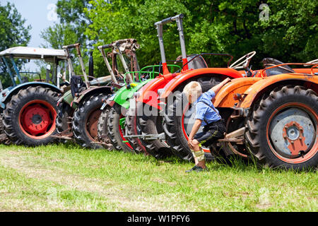 Blond boy in bavarian costume sits at Bulldog meet in the Chiemgau region on the drawbar of the tractor vintage - Stock Photo