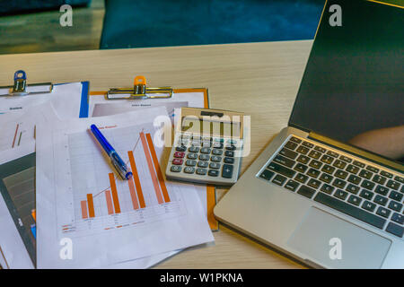 Close up of laptop graph documents on office desk - Stock Photo