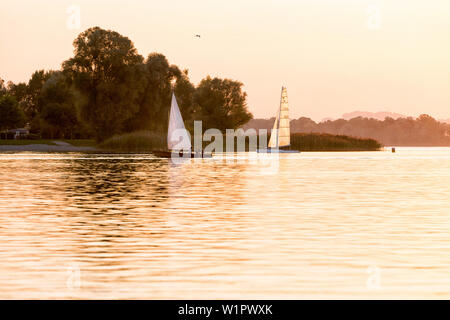 Summer evening on the shore of Lake Chiem, and plate and catamaran at the entrance to the harbor in the last evening light, rear of the Campsite Rödl - Stock Photo