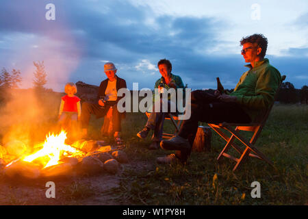 Group sitting at the campfire, Rehof Rutenberg, from dutch designers renovated old rectory, holiday apartments and garden houses, between Mecklenburg- - Stock Photo