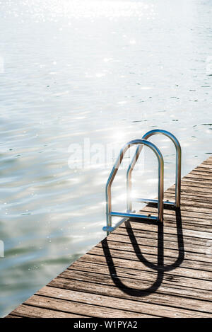 A bathing ladder with wood jetty against the light, Fort Myers Beach, Florida, USA - Stock Photo
