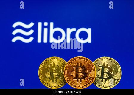 Gold Bitcoin Coins with the Facebook Libra Crypto Coin logo on background screen - Stock Photo
