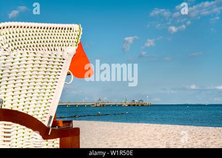 Beach with beach basket and pier, Groemitz, Baltic coast, Schleswig-Holstein, Germany - Stock Photo