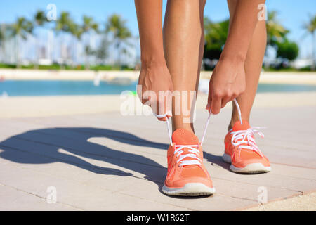 Sport fitness, Exercise running and lifestyle concept. Runner woman lacing running shoes trainers tying laces before jogging on a run. Fit healthy female feet and shoe close up. - Stock Photo