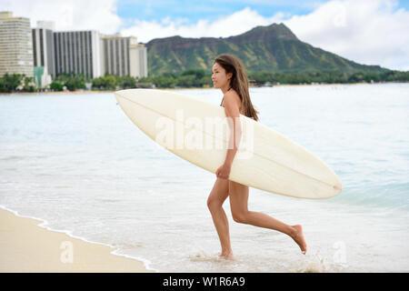 Portrait of surfer woman running surfing with surfboard having fun on Waikiki Beach, Oahu, Hawaii. Female bikini girl on surfboard smiling happy living healthy lifestyle on Hawaiian beach. Asian Caucasian model. - Stock Photo