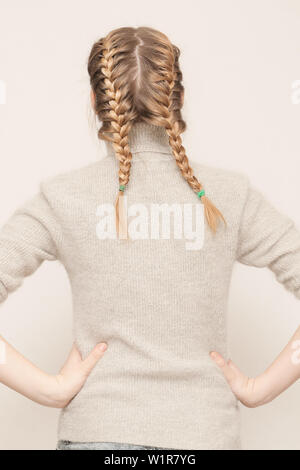 Young girl plaited one's hair in two distinct braids - Stock Photo