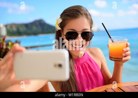 Selfie woman taking self portrait at beach bar during holidays. Young Asian adult holding smartphone camera to take a picture of herself during her summer vacations in Waikiki, Honolulu, Hawaii, USA. - Stock Photo