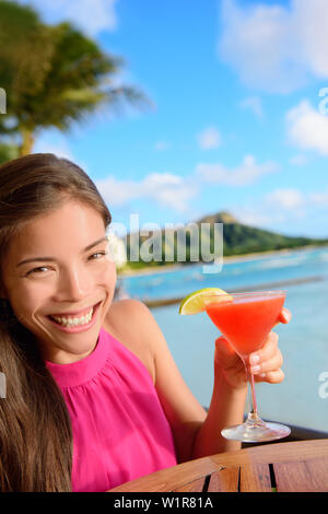 Cocktail woman drinking alcohol drinks at beach bar resort in Waikiki, Honolulu city, Oahu, Hawaii, USA. Asian girl tourist looking at camera toasting a glass of strawberry Hawaiian drink at sunset. - Stock Photo