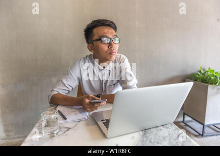 Young man using cellphone and laptop and thinking at office - Stock Photo