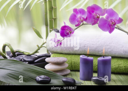 wellness environment with close-up of some bamboo stalks, aromatic candles, Stones for massage and beautiful purple orchid flowers. - Stock Photo