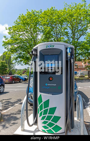 Charging point for electric vehicles situated in a car park.  Its Green credentials are emphasised by the green leaves of a tree against which it is s - Stock Photo