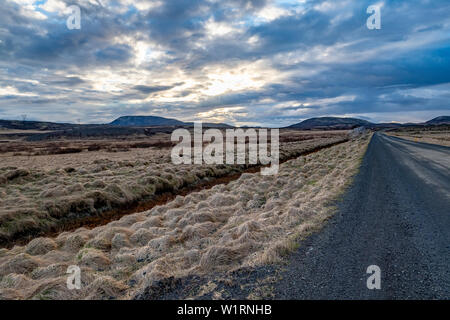Long gravel highway through the Golden Circle of central Iceland with mountains in the distance - Stock Photo