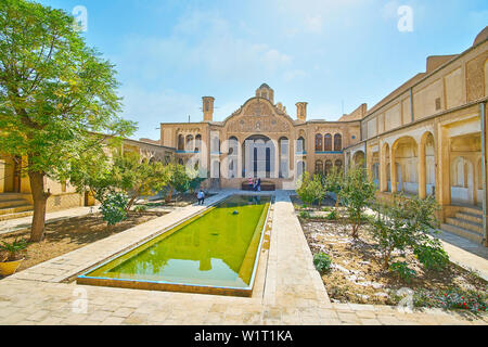 KASHAN, IRAN - OCTOBER 23, 2017: The ornate courtyard of Borujerdi Historical House with fountain, green garden and richly decorated walls and main po - Stock Photo