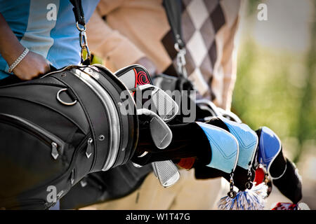 People holding golf bags - Stock Photo