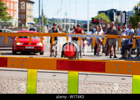 Jönköping, Sweden - Jun 22, 2019: Red light at train bars, people waiting to cross - Stock Photo