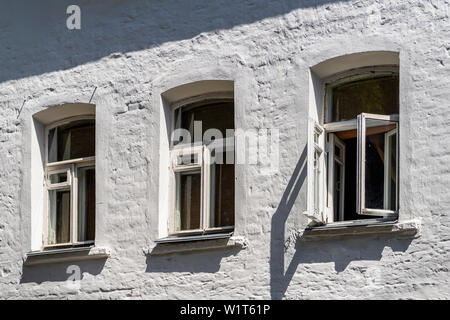 Three small windows on the facade of an old brick house painted with white paint - Stock Photo