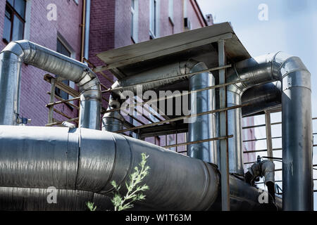Ventilation pipes on the wall of the building outside the old Industrial building of the factory - Stock Photo