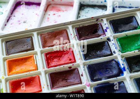 Creative artistic education concept - the box with the set of colorful watercolor paint close up