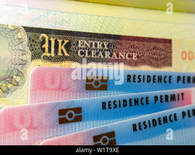 UK BRP (Biometrical Residence Permit) cards for Tier 2 work visa placed on top of UK Entry Clearance vignette sticker in the passport. - Stock Photo