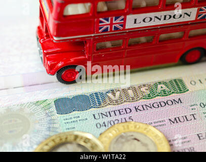 UK visa sticker in a passport surrounded by pound coins and double-decker bus model. Concept for travel and holiday. - Stock Photo