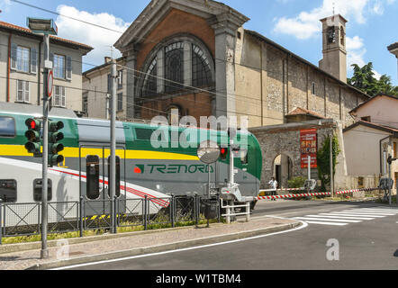 COMO, ITALY - JUNE 2019: Modern electric train passing over a road crossing as it departs from the town of Como on Lake Como - Stock Photo
